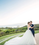 bride in vera wang ball gown hugging groom in navy blue tuxedo on lawn overlooking ocean