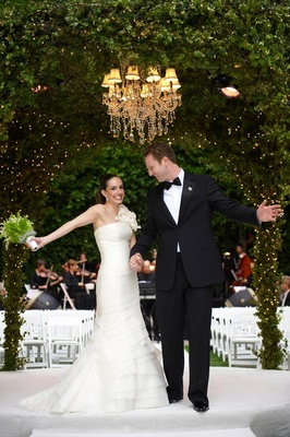 Bride and groom under ivy chuppah and chandelier