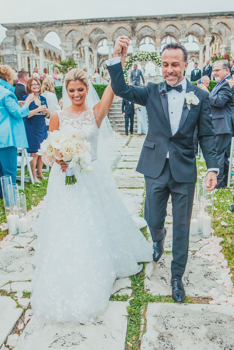 bride in lace a-line isabelle armstrong gown raising arm with groom after ceremony at bahamas