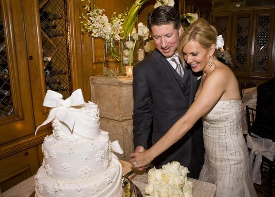Bride and groom cut wedding cake together