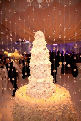 Rose cake table with tall wedding cake behind crystals