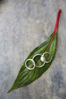 wedding bands on green leaf with vintage engagement ring side stones