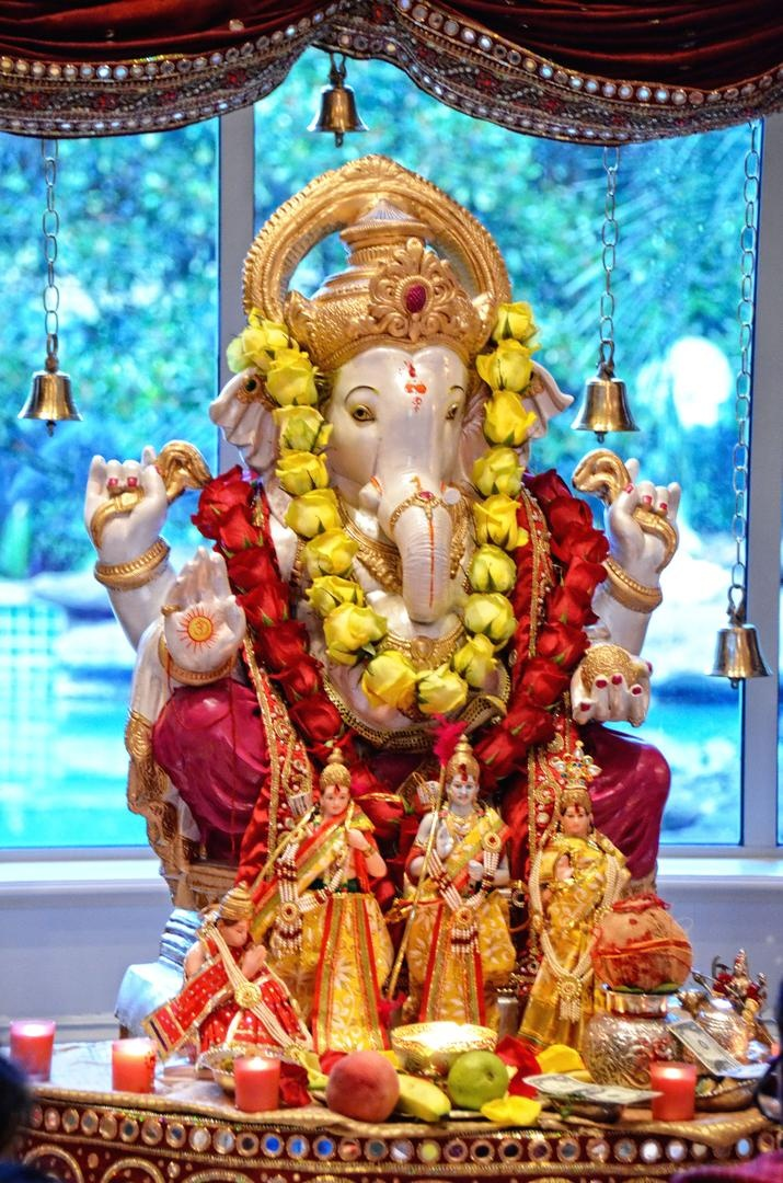 Ganesh statue with red and yellow rose garlands at a wedding ceremony