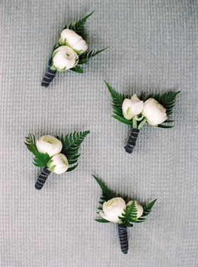 Two peony bud flower boutonniere with fern leaves and velvet wrap ribbon