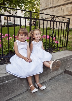 two adorable flower girls sit on ledge smiling, kicking up feet outside of wedding
