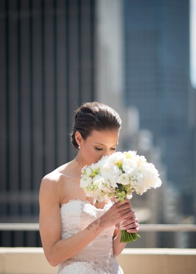 a bride smelling her bouquet made of white blooms on a rooftop in new york city