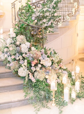 wedding reception at oheka castle grand staircase decorated with greenery candles dusty miller pink