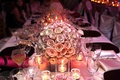 Wedding reception centerpiece of light roses surrounded by votive candles