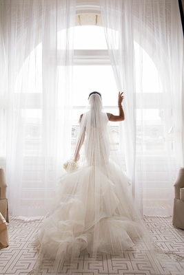 Bride in matthew christopher trumpet gown with cathedral veil bouquet looking out window city weddin