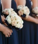 Cream and pale pink roses wrapped in navy ribbon