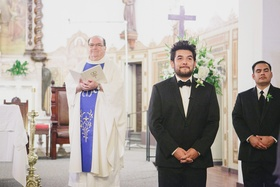 Groom watching bride walk down aisle at church wedding