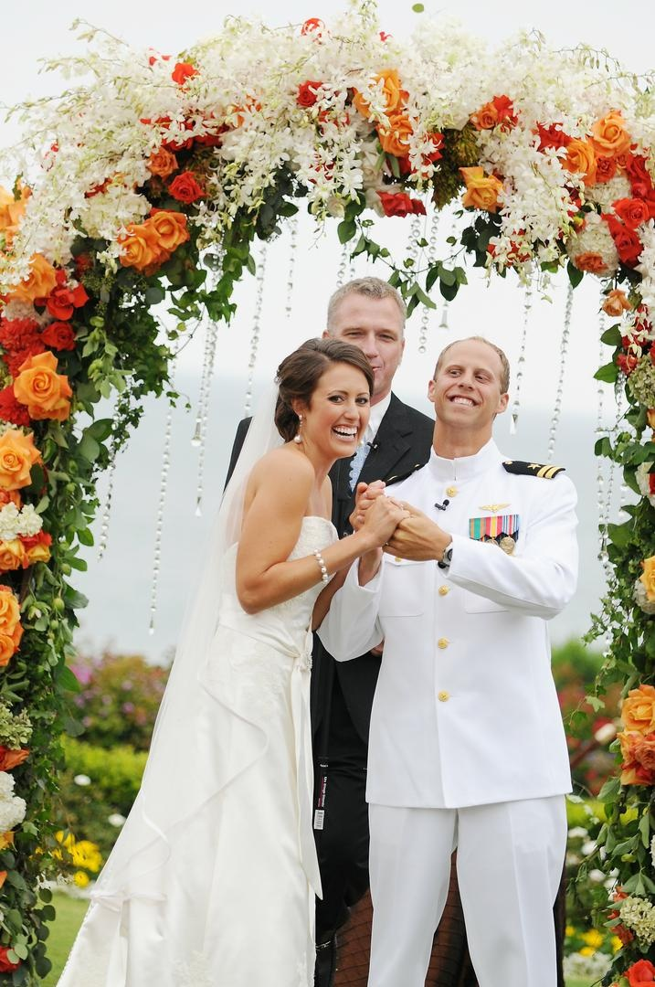 Officiant and couple under floral archway