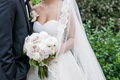 a bride and groom standing together while the bride holds a bouquet of ivory and blush rose ranuncul