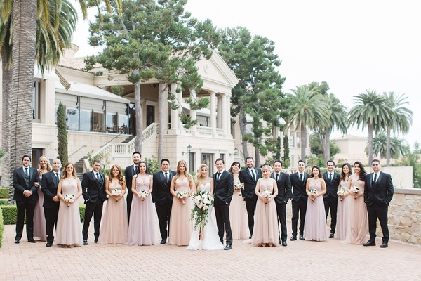 newlyweds bridesmaids groomsmen scattered pose pelican hill resort newport california wedding party