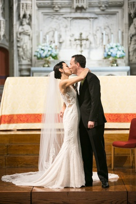 bride in rivini wedding dress and cathedral veil kisses groom during church ceremony