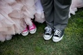 Bride in blush ruffle wedding dress with pink converse and groom in grey suit black converse