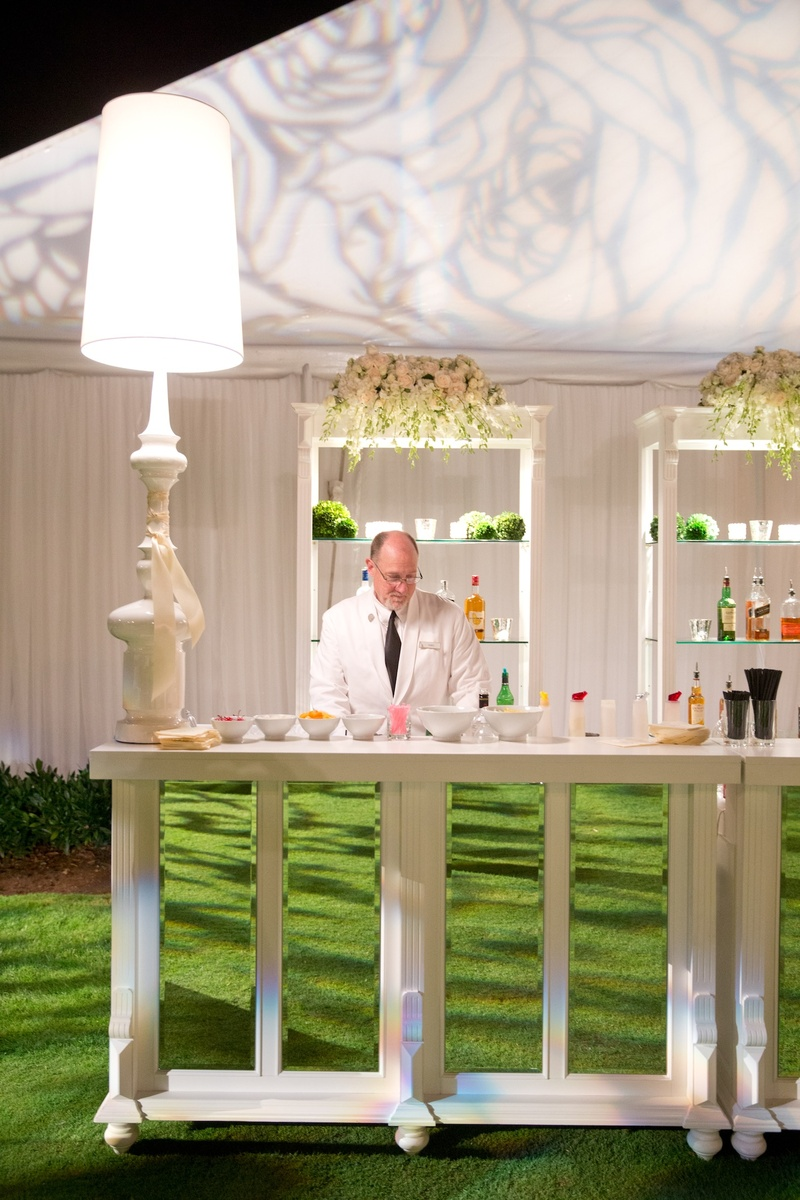 Bartender in white suit at white and mirror buffet table
