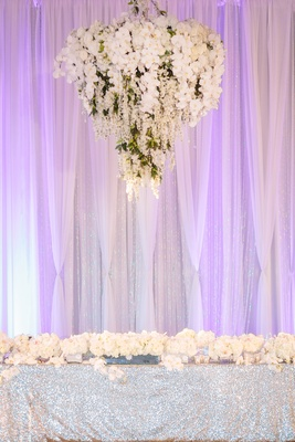 floral chandelier above head table lined with orchids and dresses with silver sequin linens