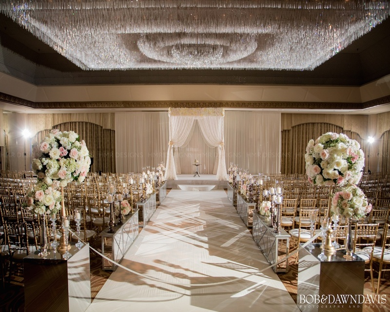 Extravagant crystal chandelier brightens up all white aisle decor & chuppah.