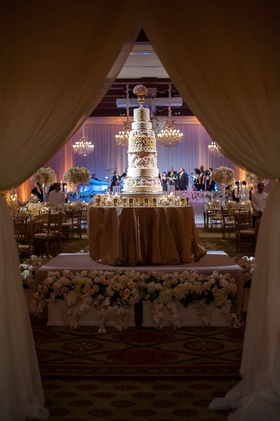 Wedding cake displayed on flower wrapped stage round gold linen table tall confection drapery