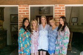 Bride in white robe and bridesmaids in robes with pink, blue, purple, red, yellow, orange flowers