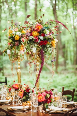 Wedding reception candelabra centerpiece with gold, red, blue, purple flowers, greenery