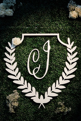 wedding reception greenery hedge wall laurel wreath monogram white flowers seating chart welcome