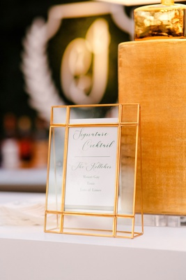 wedding reception signature cocktail menu in gold glass frame at bar monogram hedge wall
