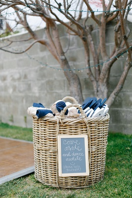 Wicker basket next to outdoor dance floor with shawls and flip-flops for wedding guests