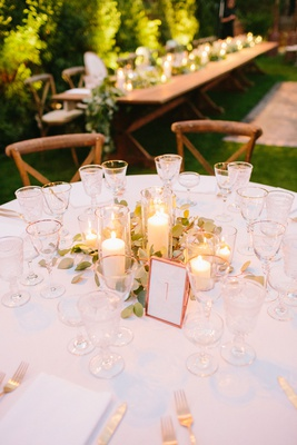outdoor wedding reception pillar candles in glass stands greenery rose gold table number gold rim