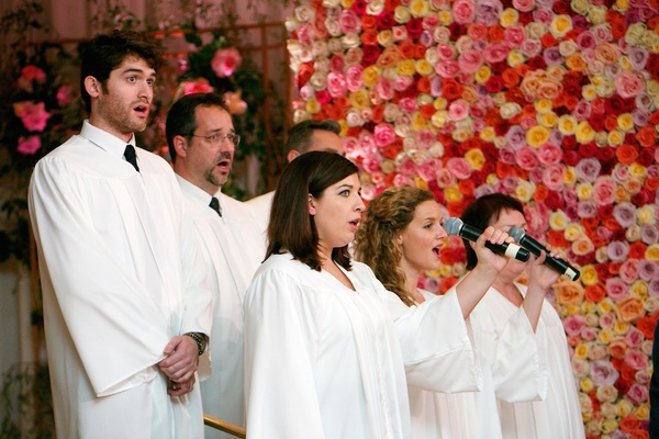 Men and women in white robes singing at wedding