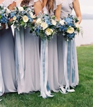 Bridesmaids in short sleeve Joanna August bridesmaid dresses with blue and white bouquet ribbons