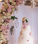 Wedding cake with lavender top tier, ruffle bottom layer, and middle layers of floral hand-painted