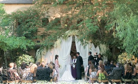 Courtyard ceremony decorated with draping, and light green and white flowers