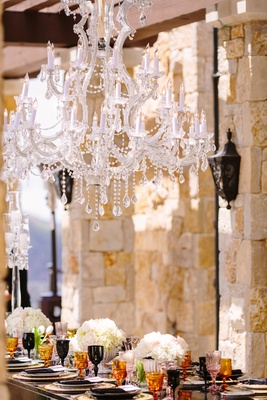 a crystal chandelier was above the black reception table