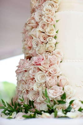 White wedding cake is decorated with cream and light pink roses studded with crystals