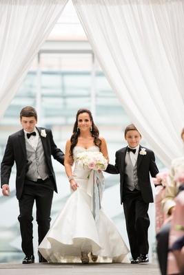 bride white trumpet dress walked down the ceremony aisle by her tow young sons in black tuxedos
