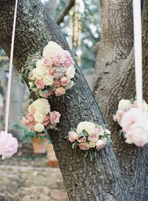 Light pink and ivory rose pomanders hanging from white ribbons on large oak tree at ceremony