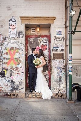 Wedding in New York City bride and groom kiss in doorway with graffiti and street art city portrait