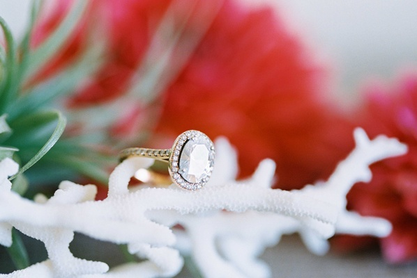 Joseph Shabani designed oval cut engagement ring with halo and pave yellow gold band on white coral