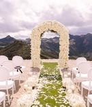 malibu rocky oaks ceremony, white chairs, ivory floral arch