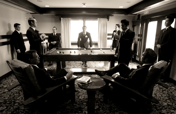 Black and white image of groomsmen playing pool