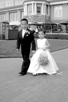 Black and white photo of flower girl carrying a pomander bouquet and boy