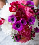 bright bridal bouquet made up of pink purple and white flowers accented by green foliage