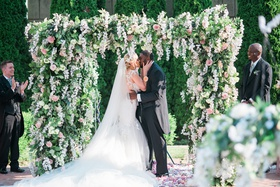 bride in galia lahav bridal gown kissing groom under lush ceremony arbor, donathan hurley survivor