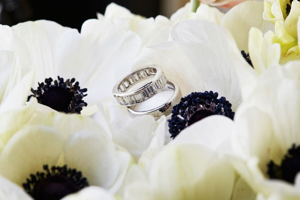 Wedding ring with diamonds and polished ring on top of japanese anemone flowers