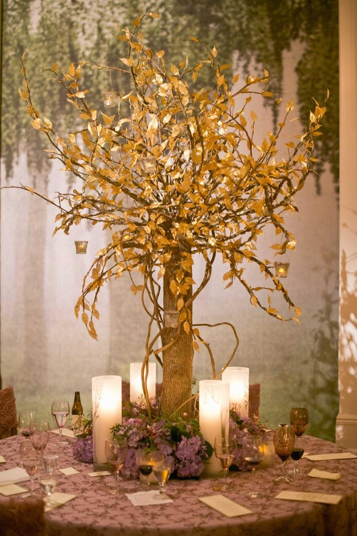 Woodsy wedding with tree trunk centerpiece and gold leaves