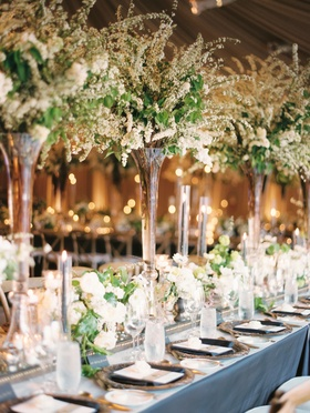 Tall centerpiece flowers with small short flowers in between on mirror runner candles dark details