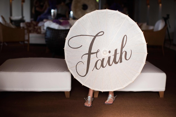 Flower girl holding white parasol with Faith in calligraphy