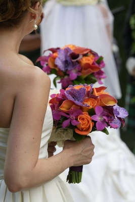 Bridesmaid holds bouquets of colorful orange and purple flowers